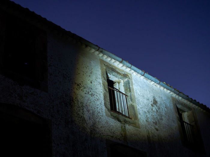 Low angle view of old building against clear sky at night