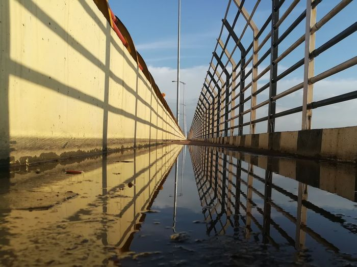 Reflection of built structure in water against sky