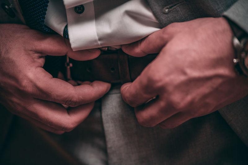 Midsection of businessman adjusting belt