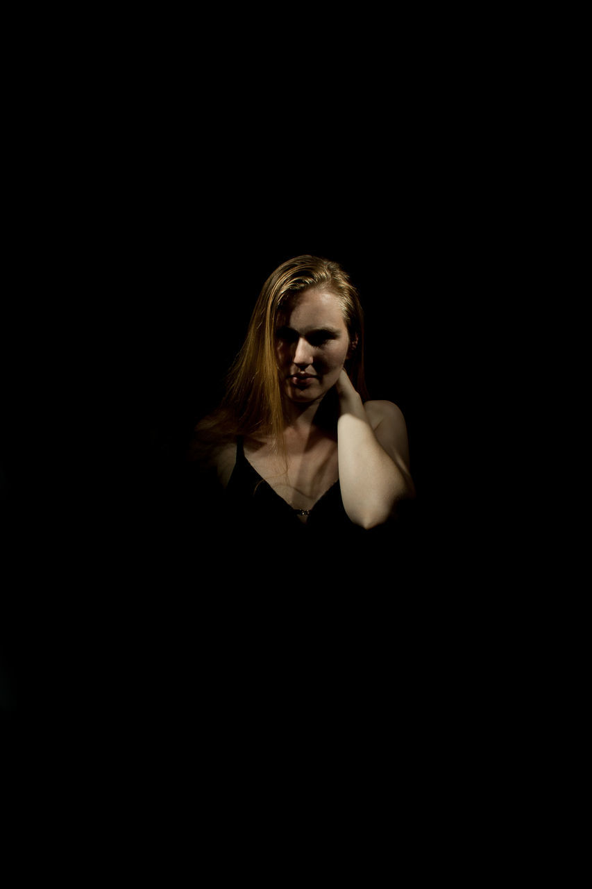 Beautiful Woman With Hand On Neck Against Black Background