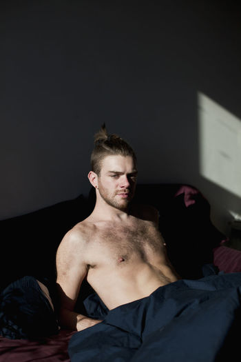 Portrait of young man sitting on bed at home