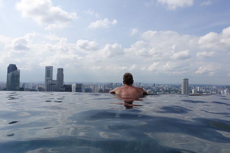 Rear view of shirtless man in swimming pool against sky