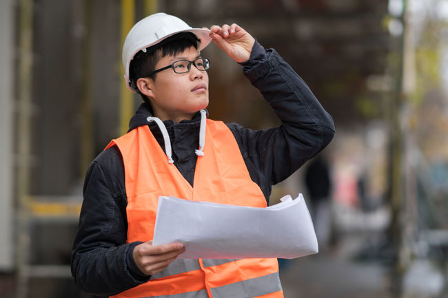ARCHITECT Architects Growth Plant Blueprints Construction Site Development Engineer Engineering Hardhat  Helmet Manual Worker Men Occupation Outdoors People Project Protective Workwear Real Estate Real People Reflective Clothing Safety Working