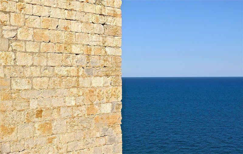 Brick wall by sea against clear blue sky