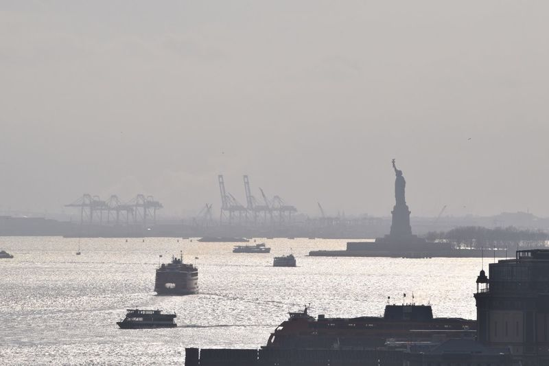 Silhouette Statue Of Liberty In Hudson River Against Sky