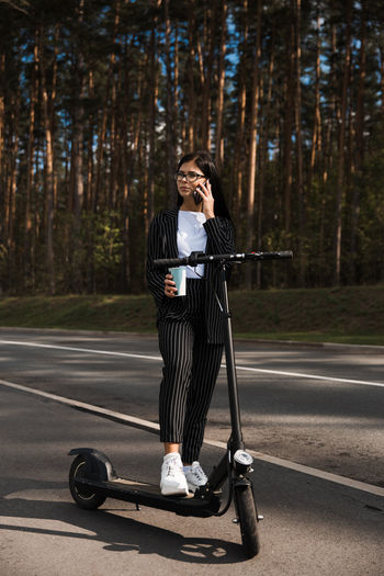 Woman talking over smart phone while standing on road against trees