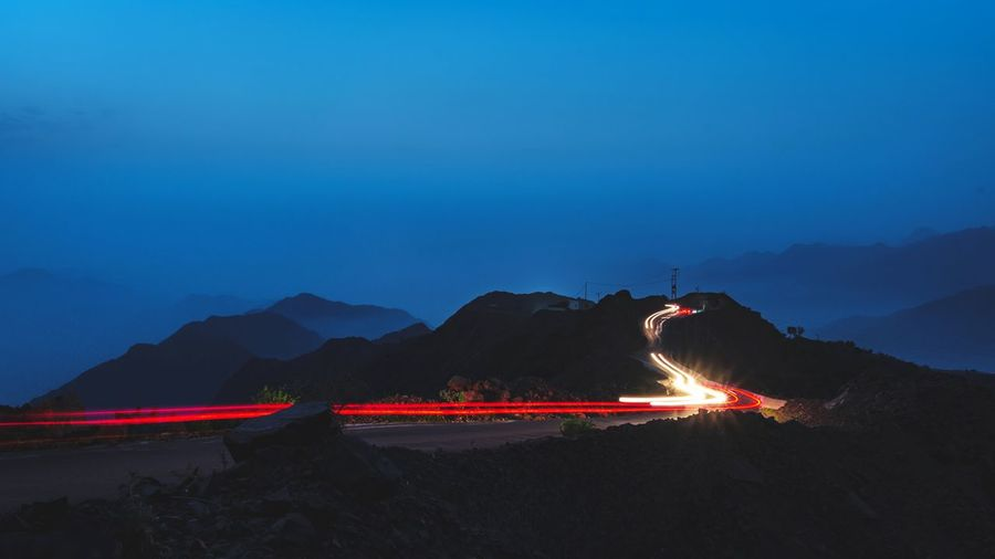 Light trails on mountain against sky at night