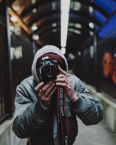 @milohale Holding One Person Real People Photography Themes Camera - Photographic Equipment Photographing Photographer Photographic Equipment Leisure Activity Technology Exploring EyeEm Best Shots EyeEm Streetphotography Focus On Foreground Lifestyles Lens - Optical Instrument Digital Camera Warm Clothing Night London City City Life Tunnel Portrait