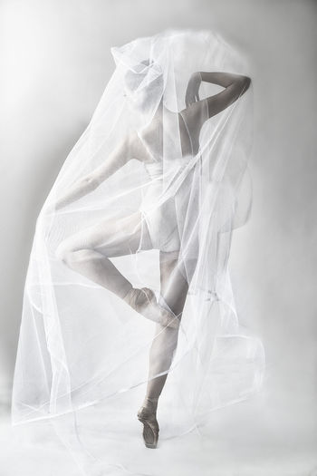 Woman wrapped in textile while dancing against white background