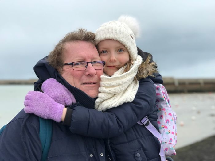 Close-Up Portrait Of Girl Embracing Grandfather Against Sea During Winter