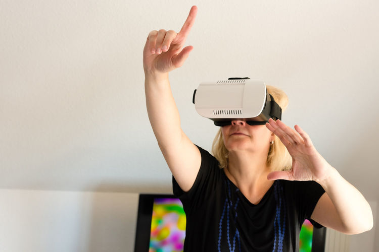 Middle-aged woman looking through virtual reality glasses