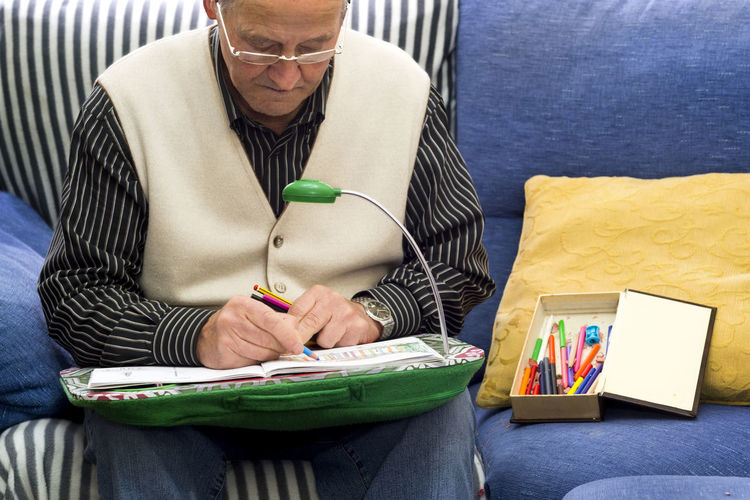 Senior Man Drawing On Book While Sitting On Sofa At Home