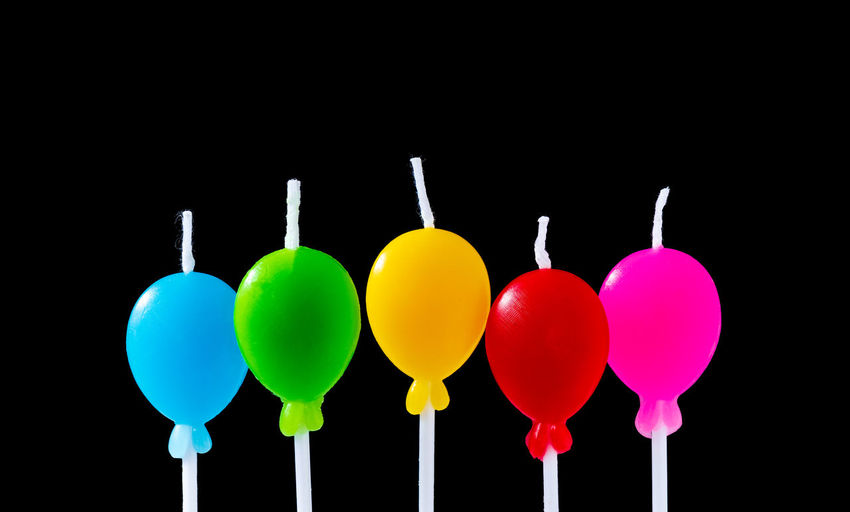 Close-up of multi colored balloons against black background
