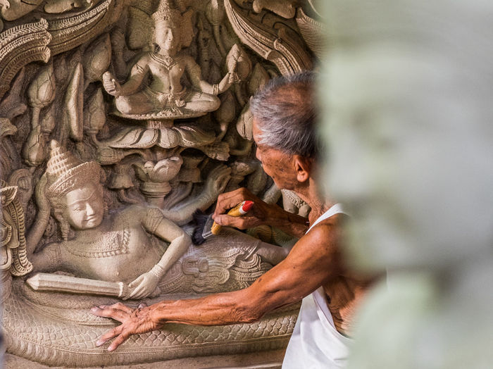Side view of senior man carving statues