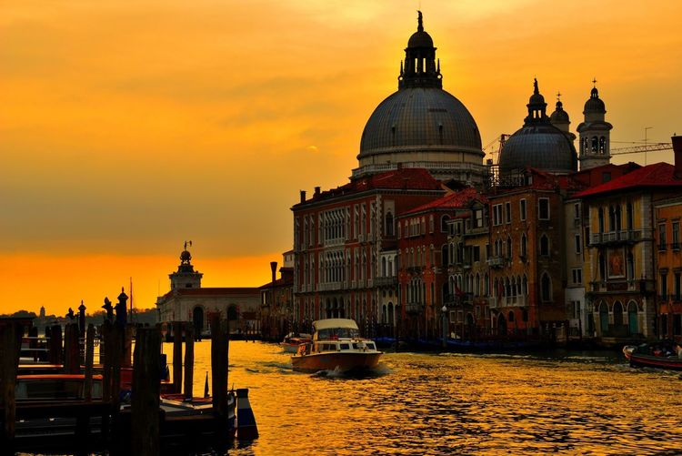 Grand canal by santa maria della salute against sky during sunset