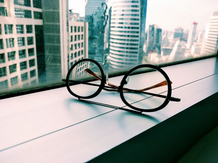 Close-up of eyeglasses on window sill against buildings in city
