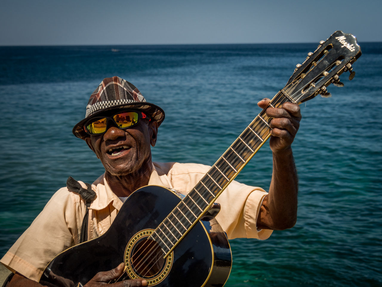 guitar, music, musical instrument, sea, guitarist, playing, acoustic guitar, musician, water, plucking an instrument, arts culture and entertainment, outdoors, real people, one person, performance, horizon over water, nature, fretboard, day, people