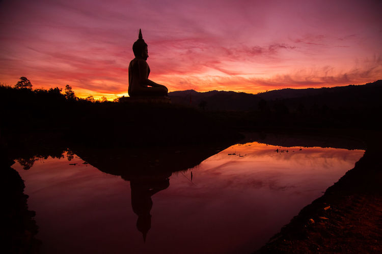 Silhouette of statue at sunset