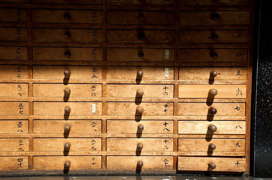 a set of drawers hold thousands of fortunes outside a temple in Tokyo, Japan. Backgrounds Close Up Japanese Text Chinese Numbers Fortune Telling Make A Wish Chance Objects In A Row Repetition Backgrounds Full Frame Yellow Wood - Material Locker Room Pattern Shadow Close-up Wooden Closed Door