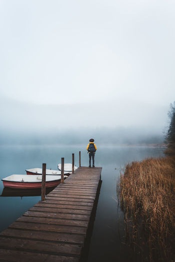 Sky Rear View Water Pier One Person Direction The Way Forward Nature Wood - Material Full Length Beauty In Nature Jetty Leisure Activity Fog Real People Scenics - Nature Men Outdoors Diminishing Perspective Fog Over Water Backpack Hiking Fall Beauty Hat Boats