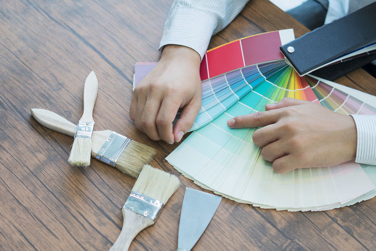 Midsection of design professional choosing color swatch on table