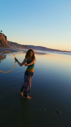Portrait of woman exercising with plastic hoop at beach