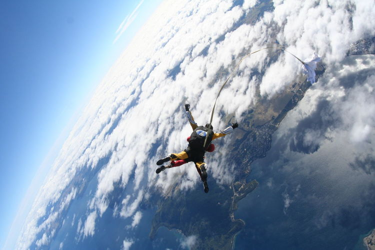 Aerial View Of Friends Skydiving Over Clouds And Landscape