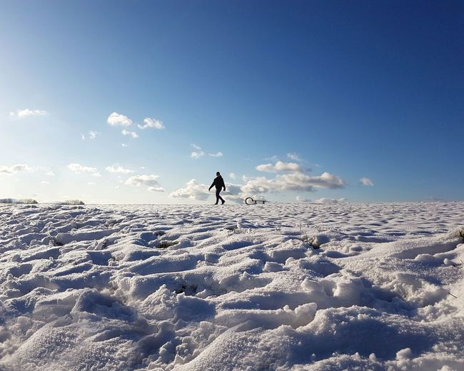 Man on snow covered land against sky