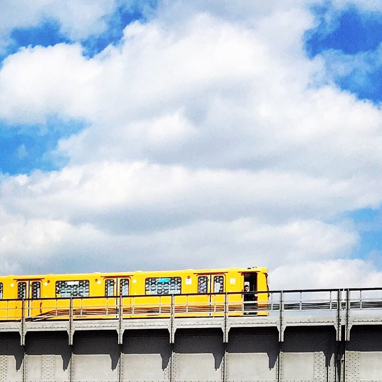 cloud - sky, sky, transportation, rail transportation, train, train - vehicle, public transportation, mode of transportation, architecture, no people, nature, built structure, day, passenger train, bridge, yellow, outdoors, connection, bridge - man made structure, land vehicle, railroad car