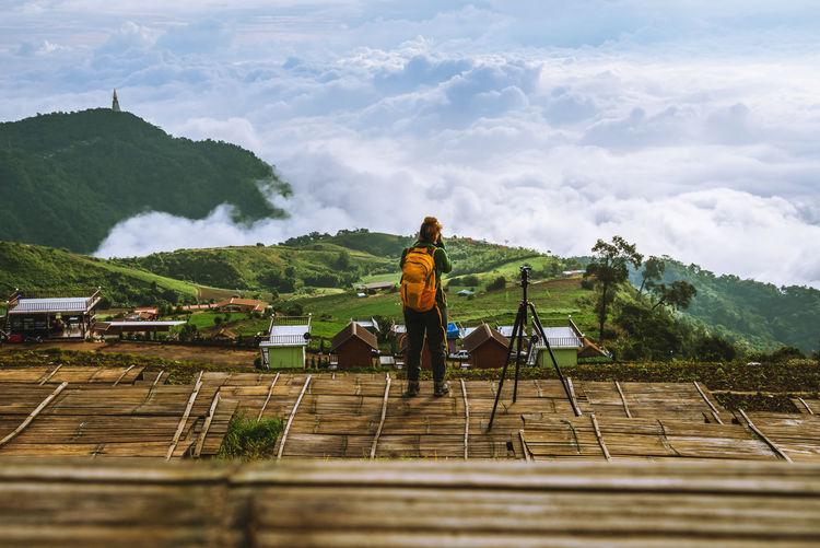 Rear view of woman photographing against landscape against cloudscape