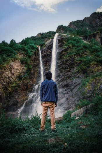 Rear view of boy looking at waterfall in forest