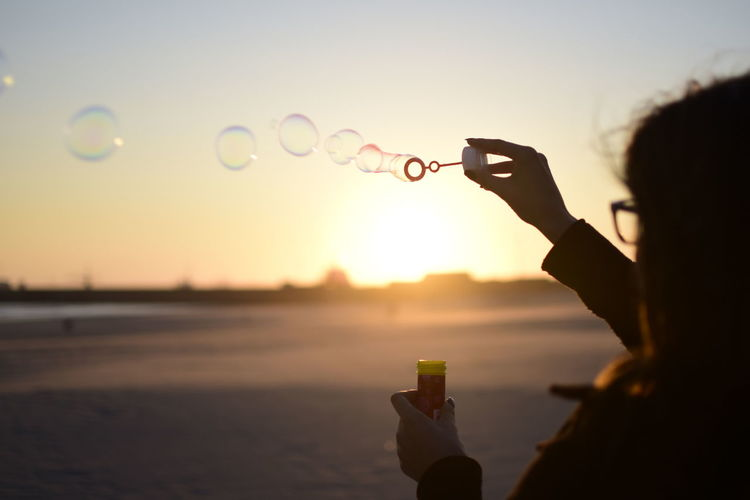Scenic view of person blowing bubbles in air against clear sky