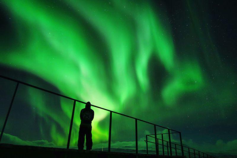 Rear view of man standing against aurora borealis