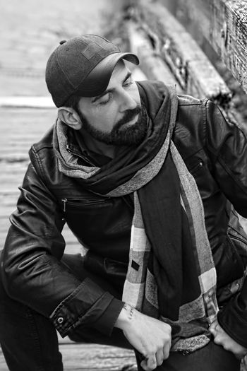 Close-up of bearded mature man wearing scarf and jacket while kneeling on footbridge