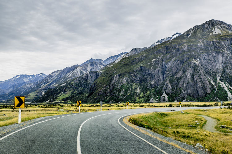 Road between rocky mountains in Mount Cook National Park, New Zealand Road Mountain Transportation Scenics - Nature The Way Forward Sky Cloud - Sky Beauty In Nature Nature Direction Day Outdoors Landscape Mountain Range Environment New Zealand