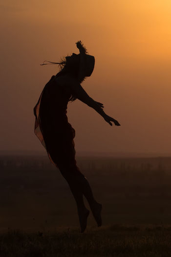 Freedom Happiness Hat Summertime Sunlight Beautiful Woman Beauty Cheerful Evening Female Flying Girl Jumping Lifestyles Light And Shadow Motion Nature One Person Orange Color Outdoors Silhouette Sunrise Sunset Women Young Women