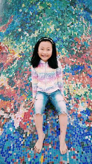 Portrait of smiling girl sitting on mosaic floor