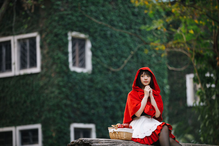 Full length of woman standing by red basket