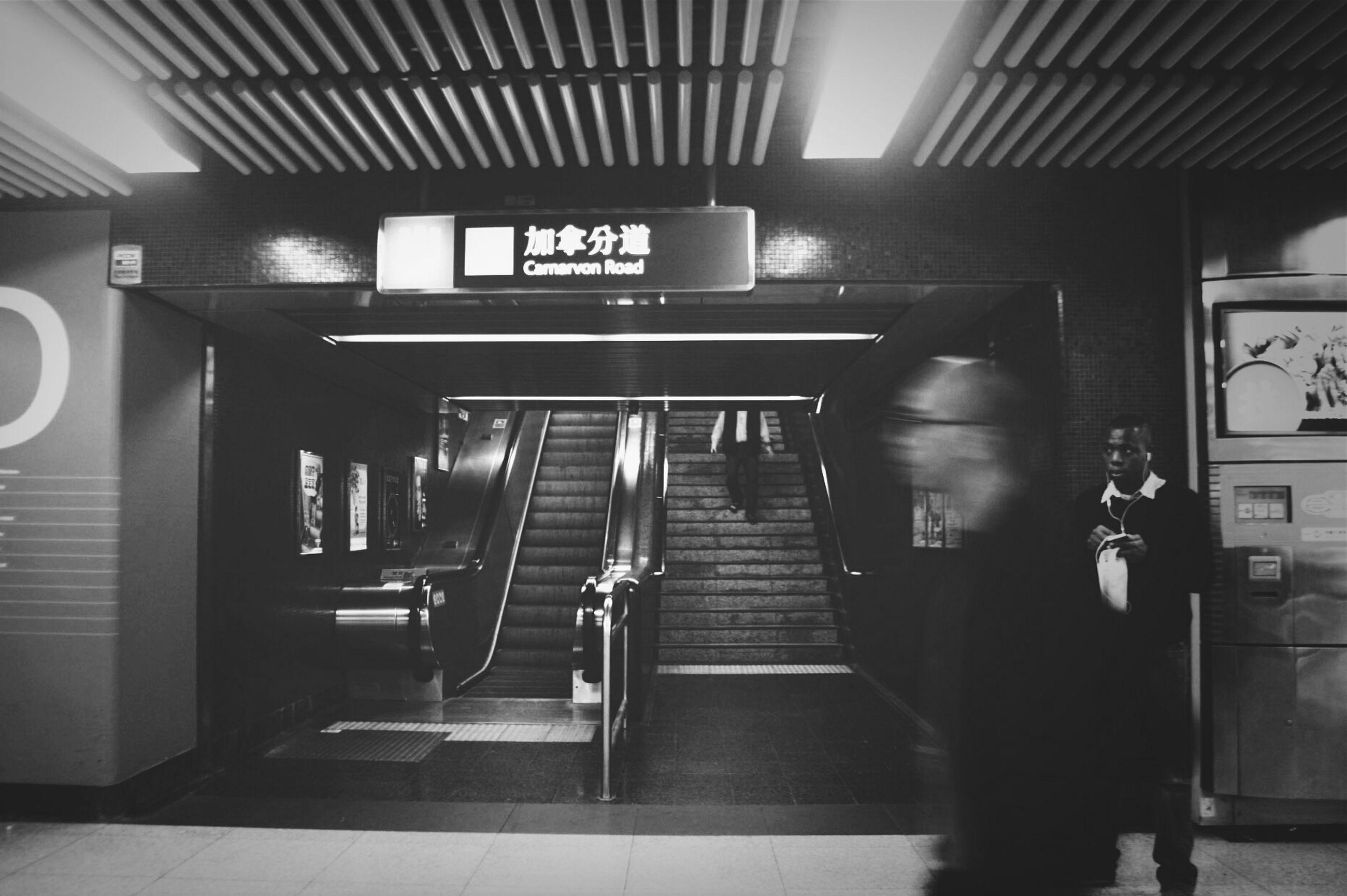 indoors, illuminated, subway, subway station, text, architecture, railroad station, ceiling, communication, built structure, men, public transportation, western script, transportation, modern, person, railroad station platform, technology