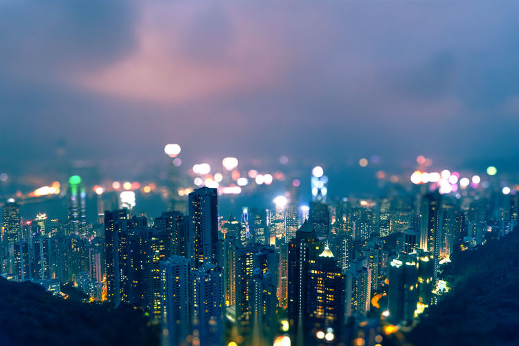 Tilt shift image of illuminated cityscape against cloudy sky at night