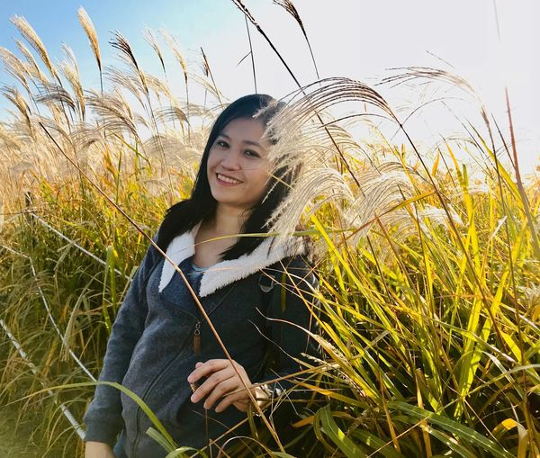 Portrait of smiling mid adult woman standing on grassy field against sky
