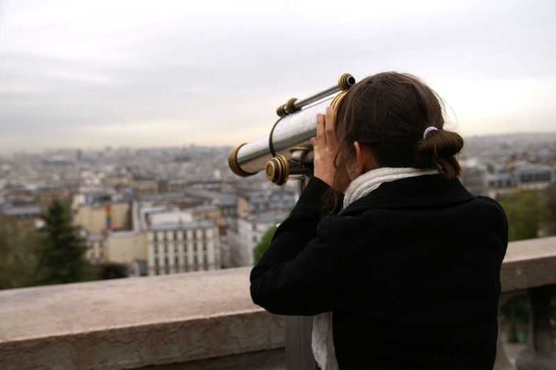 Rear View Of Woman Looking Through Telescope While Standing On Building Terrace
