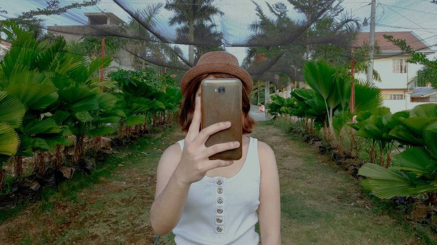 Midsection of woman using mobile phone against plants