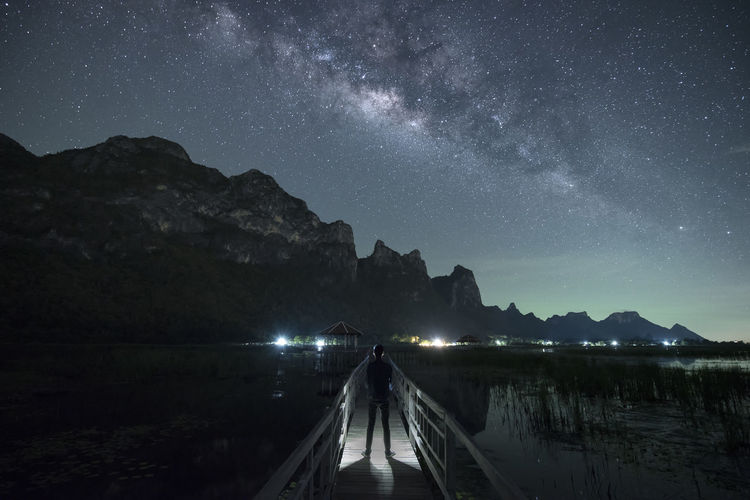 Man standing on footbridge over lake against sky at night