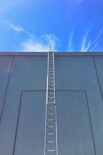 Low angle view of ladder by wall against sky