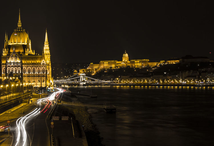 River Amidst Illuminated Hungarian Parliament Building And Buda Castle Against Clear Sky At Night