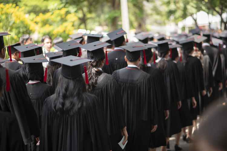 Rear view of people in graduation gown standing outdoors