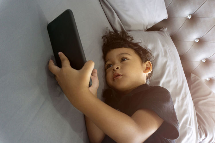 Wireless Technology Technology Furniture Bed Real People Lying Down Relaxation Indoors  High Angle View Communication Connection One Person Childhood Lying On Back Child Digital Tablet Lifestyles Portable Information Device Leisure Activity Boys Innocence Smart Phone Phone