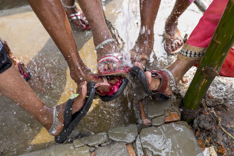 A group of Indian women wash their feet under a communal tap at the Sonepur Mela festival, Bihar Adults Only Bihar Close-up Cold Water Feet Hajipur Human Body Part India Real People Sandals Sonepur Sonepurmela Splash Splashing Tap Toes Travel Travel Photography Wash Washing Feet Water Women