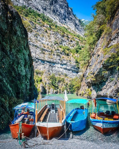 Boats moored on rocks by sea